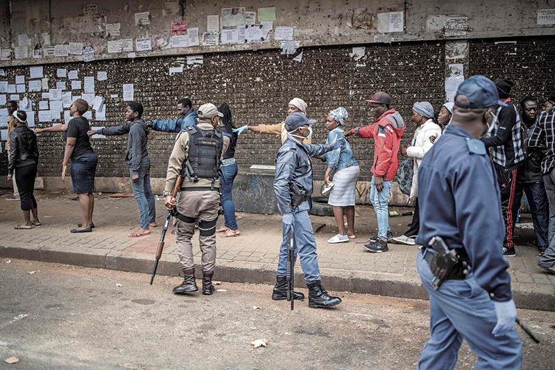 Mail and Guardian Piece on KRISP Keep it safe: Police enforce social distancing between people outside a supermarket in Yeoville, Johannesburg